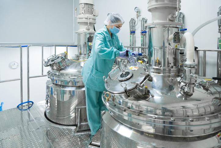 A technician checking a stainless steel bioreactor.