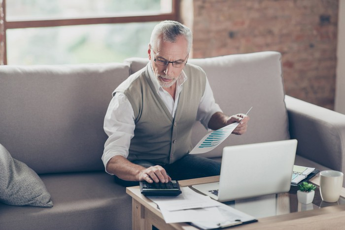 Older man on a couch holding a document and using a calculator, with a laptop in front of him