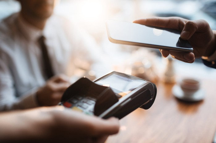 A person holding a smartphone near a mobile payment device