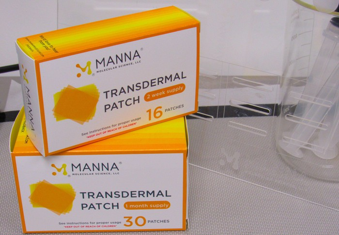 Two orange boxes labeled Manna transdermal patch, on a gray table.
