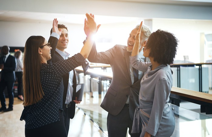 Four business people giving high fives
