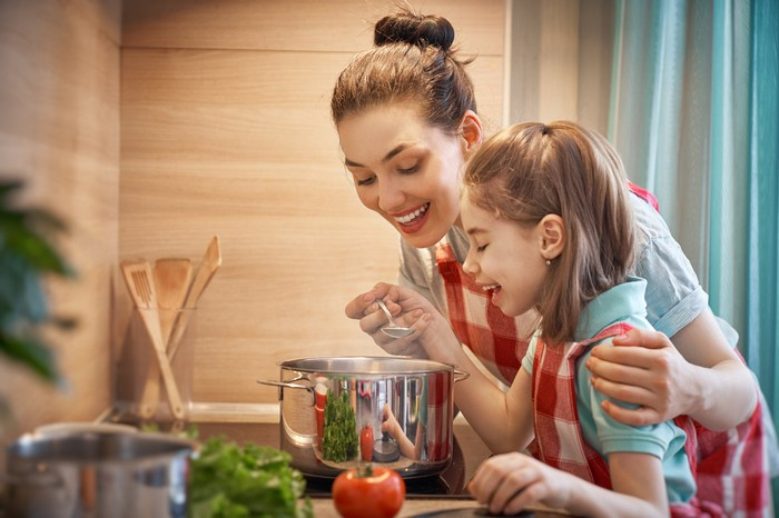 Woman and child heating up soup together