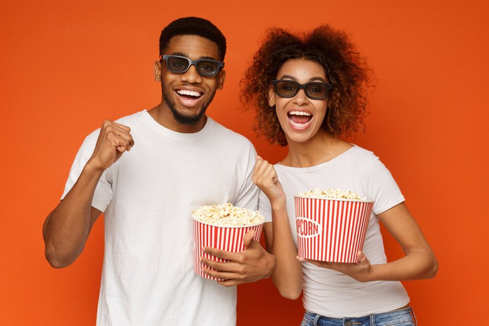 Two moviegoers with popcorn in their hands.