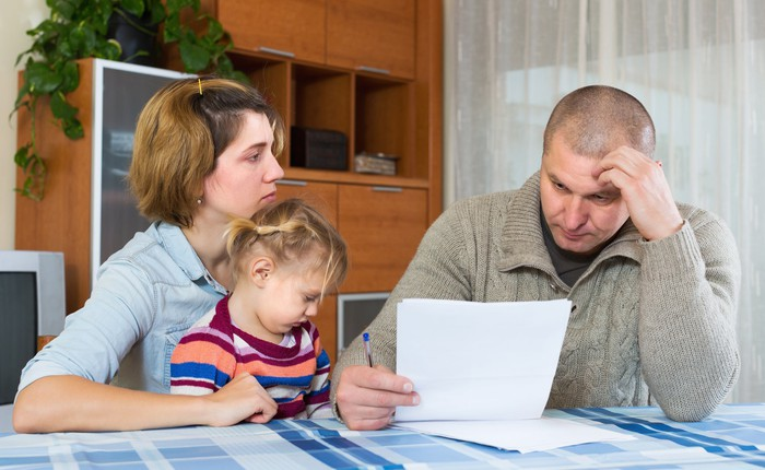 Man reading a document while woman sits next to him with young girl on her lap