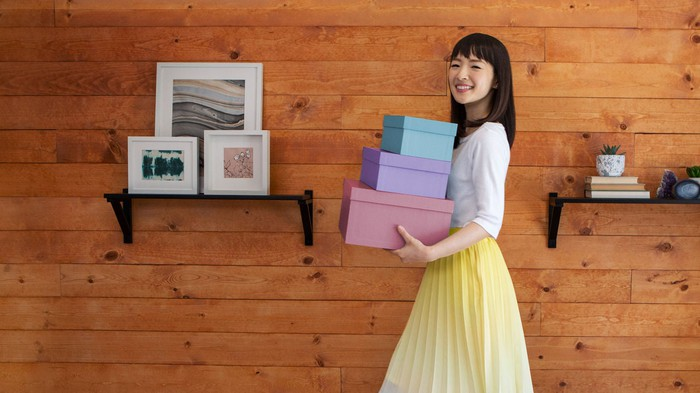 Marie Kondo holding three boxes standing in front of a wall with shelves of pictures and books.