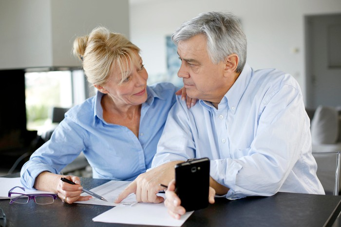 An elderly couple sits looking over a document together.