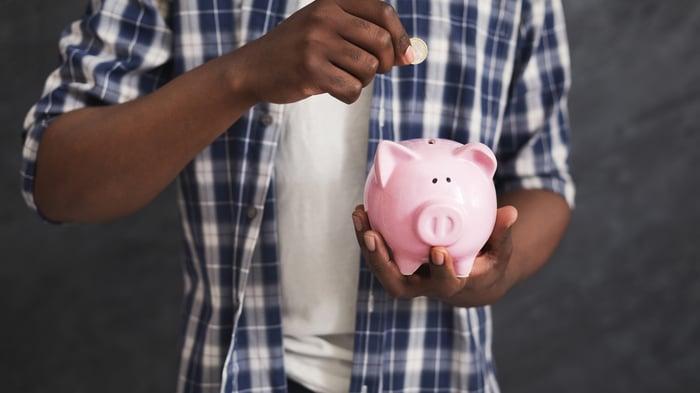 Man dropping coin into piggy bank