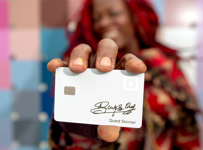 Square card being held by artist Quest Skinner