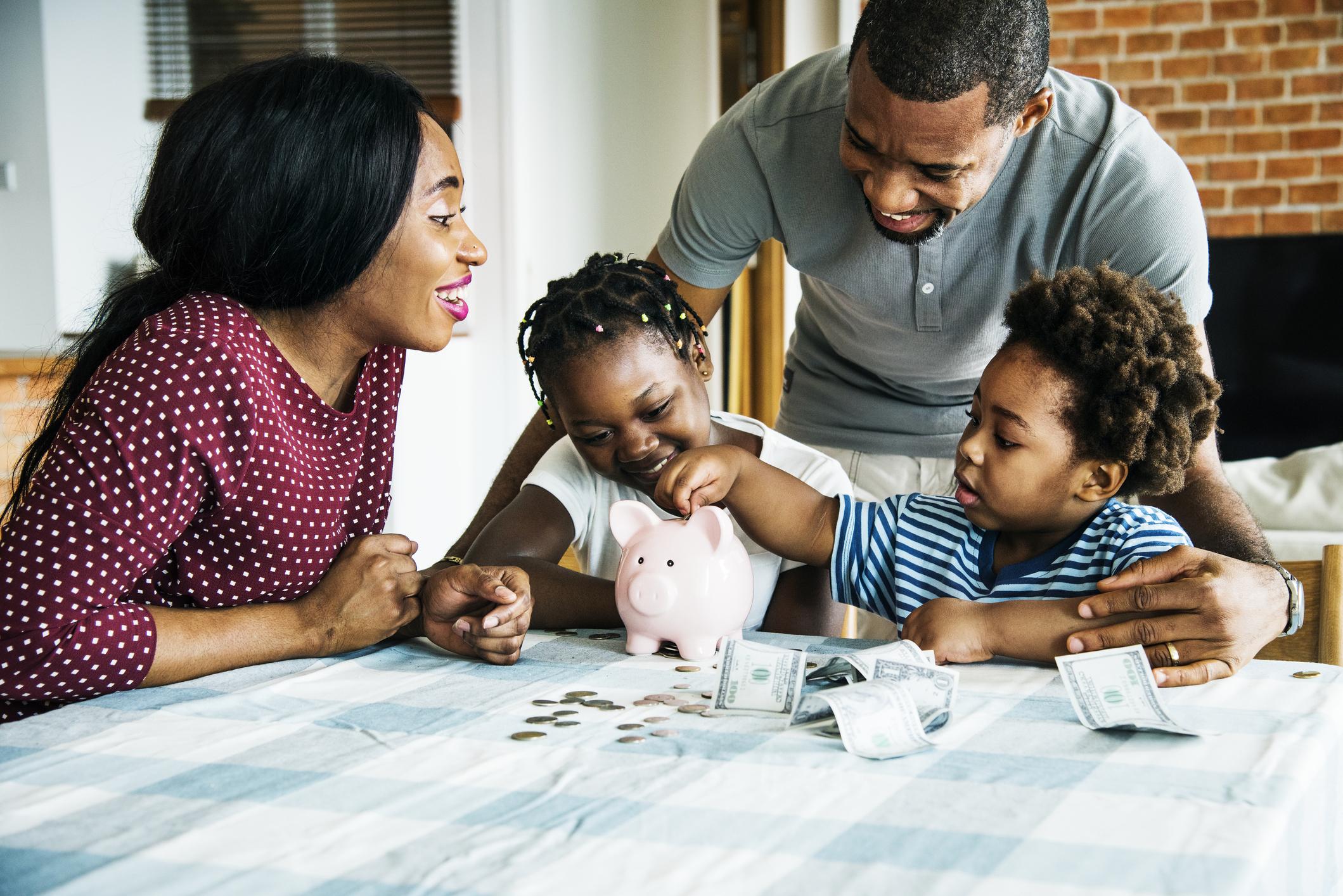 A family puts money into a piggy bank.