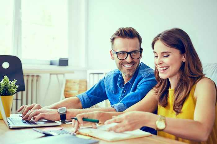 Smiling couple at table; man is typing on laptop and woman is flipping through a document