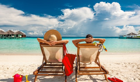 man and woman relaxing in lounge chairs on a beach in the Maldives -- mature couple vacation early retirement