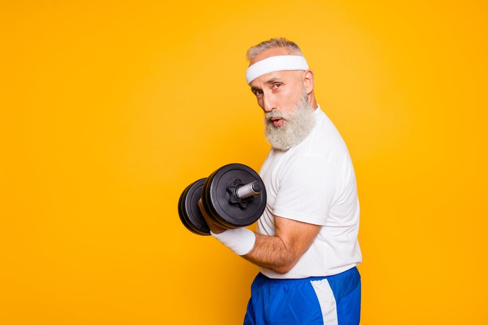 An older man in workout clothes lifting a dumbbell with his arm