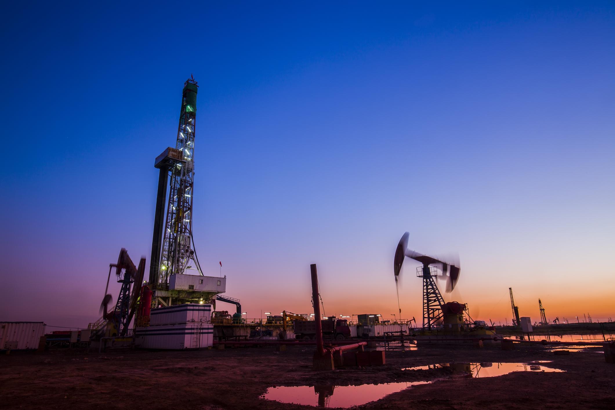 Drilling rig and pumpjack at dusk.