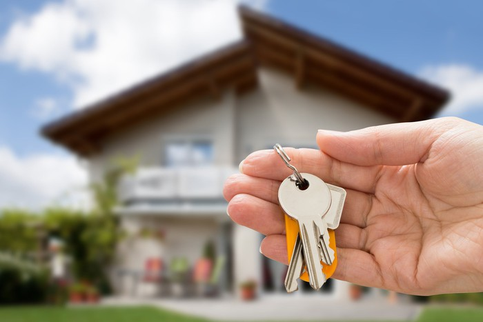 Person holding a set of keys with a house in the background