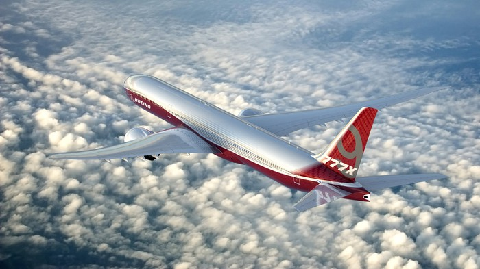 A rendering of a 777-9 flying above clouds