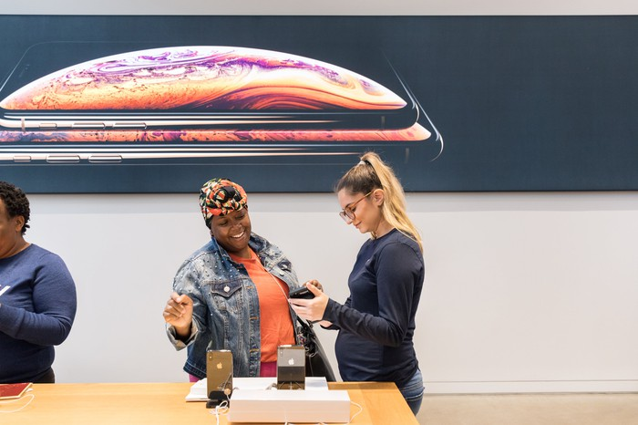 A customer (middle) with Apple store employees on both her left and right.