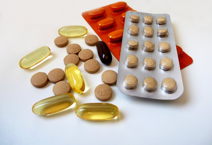Supplements in several forms (tablet, capsule, softgel) on a table.