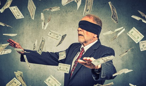 Blindfolded businessman chasing dollar bills