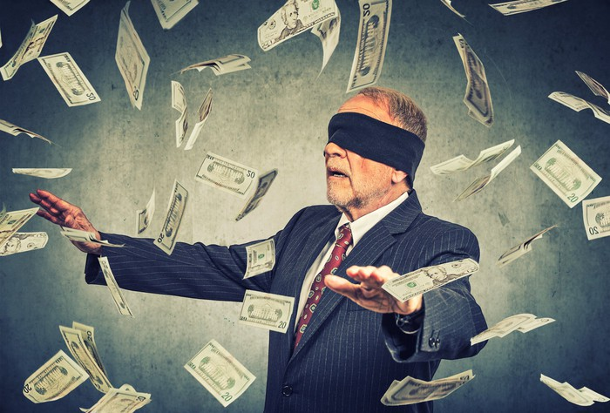 A blindfolded businessman chasing twenty-dollar bills floating in the air around him.