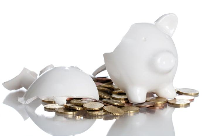Broken piggy bank with spilled coins.