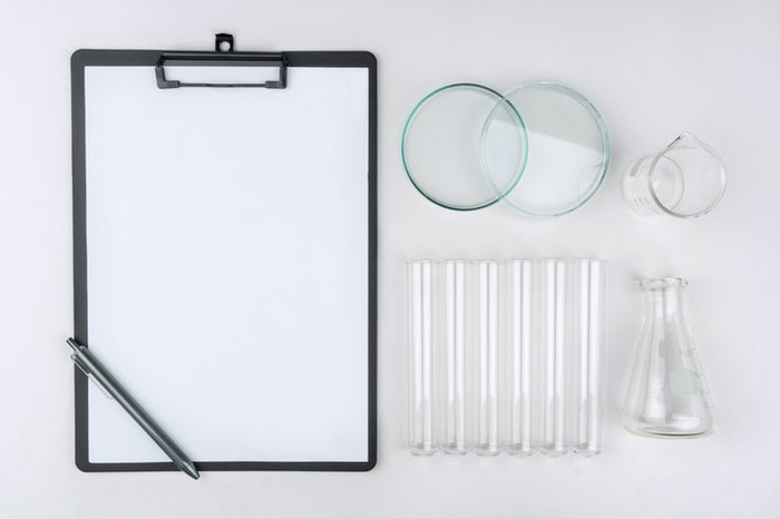 A clipboard and various glassware from a lab.
