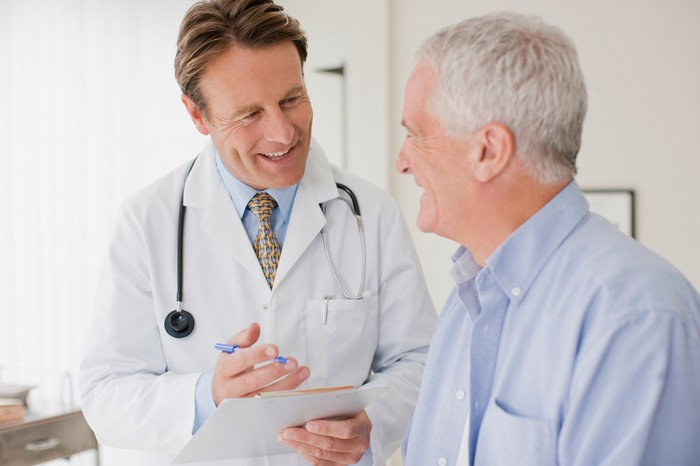 A doctor talks to an older man, both smiling, in an office setting.