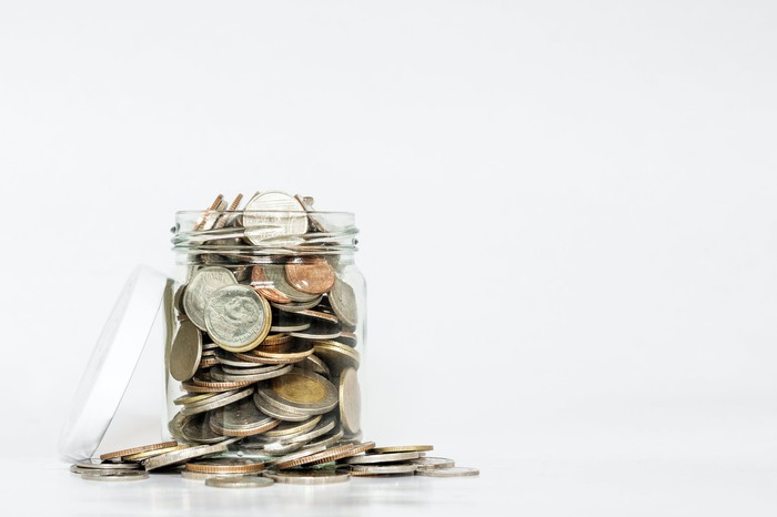 Glass jar overflowing with coins
