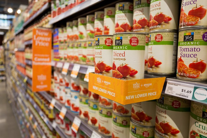 A shelf of canned tomatoes at Whole Foods with an Amazon notice about lower prices