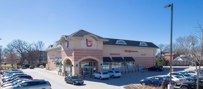 Walgreens store with surrounding parking lot, including one to two dozen cars.