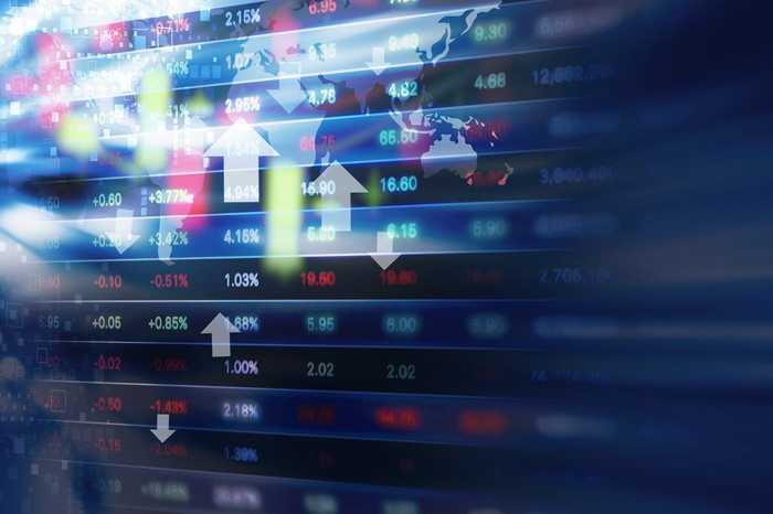 Stock market data and arrows on a colorful display.