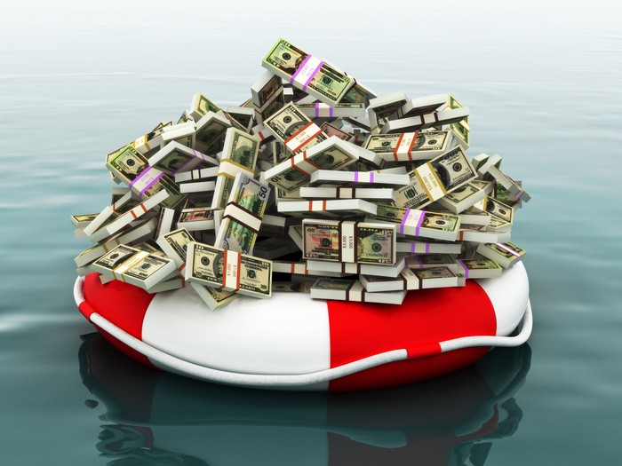 Pile of money floating in a life preserver.