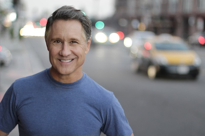 Smiling man with cars faded in the background