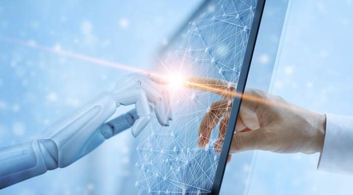 A robotic hand touching a human hand through a screen.
