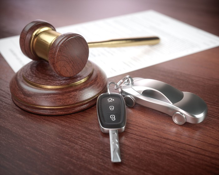 A gavel next to a miniature car attached to car keys.
