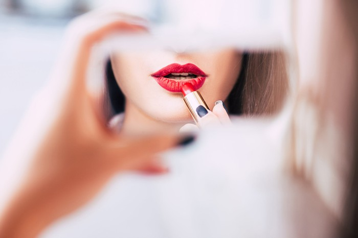 A woman applying lipstick in a handheld mirror.