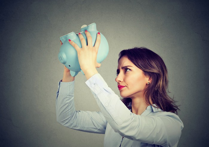Person shaking an empty piggy bank.