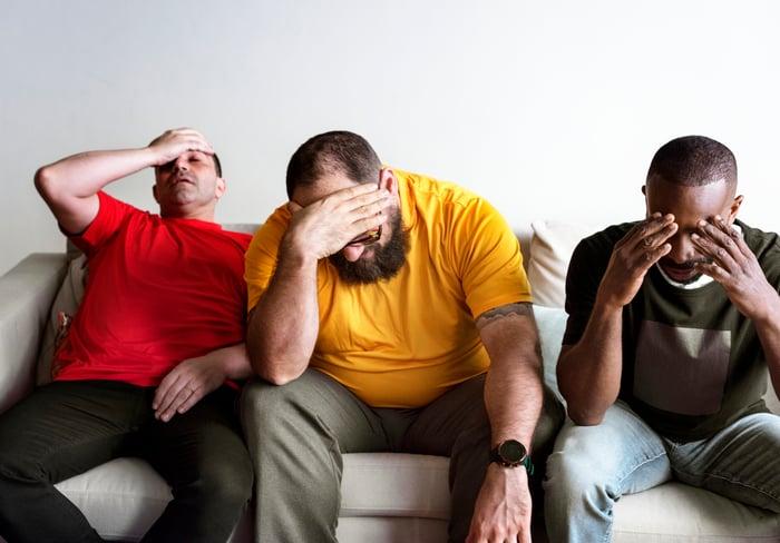 Three distressed guys on a sofa.