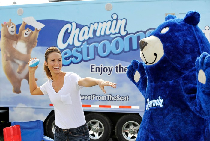 Person throwing a blue football at a blue bear, with Charmin truck in background.