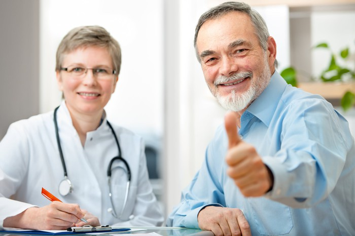 A senior man giving the thumbs-up sign while sitting next to a female doctor with a stethoscope around her neck.