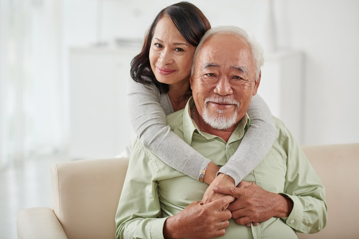 A happy senior couple -- the man is sitting on a couch and the woman is embracing him while he holds her hands.