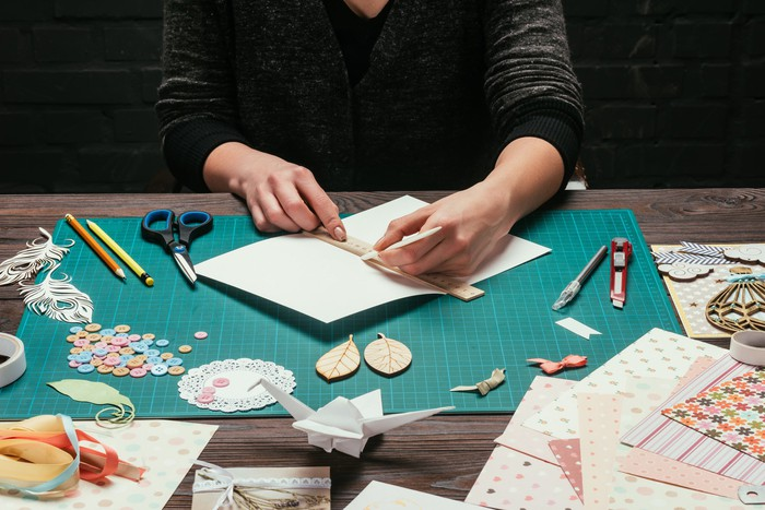 A person sitting at a table with scissors, pencils, paper, and various other crafting items.