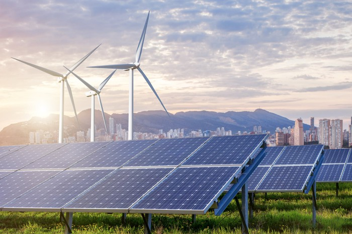 Wind turbines and solar panels with a city, mountains, and bright sun in the background.