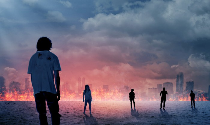 Panorama of a burning city with a handful of zombies shambling toward the flames.