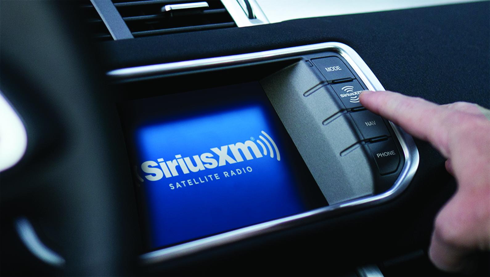 A driver pressing a button on their Sirius XM in-car radio display.