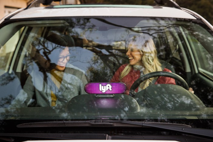 Two smiling women sitting in the front seat of a car with the Lyft logo mounted on the dashboard