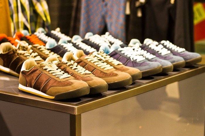 Shoes lined up on a table in a store.