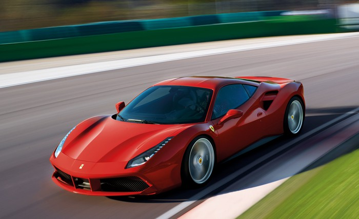 A red Ferrari 488 GTB, a mid-engined exotic sports car, shown at speed on a race track