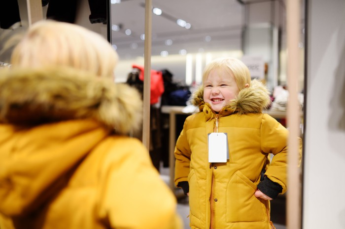 A reflection in a mirror of a boy trying on a coat.