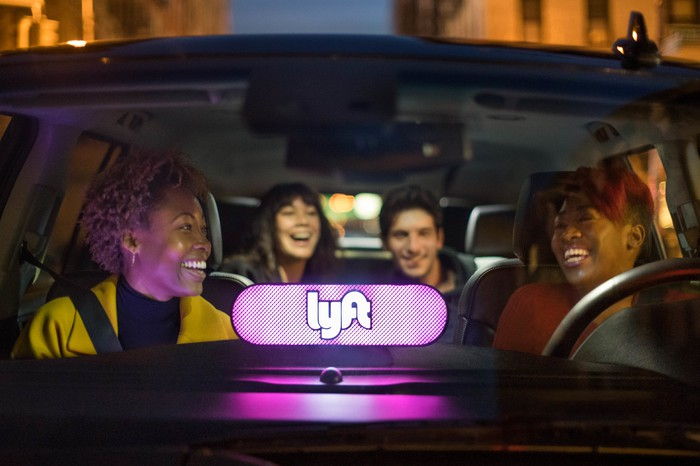 A lighted Lyft logo mounted on the dashboard of a car with driver and passengers laughing