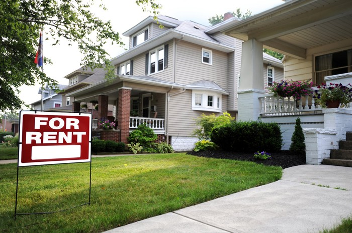 House with for rent sign on the lawn.